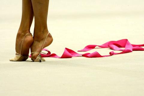 гимнастка выполняет упражнения с лентой