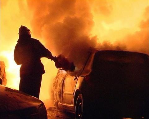 Пожарный тушит автомобиль