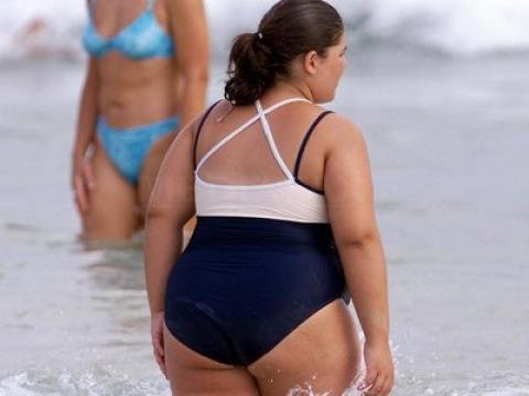 Полная женщина заходит в воду