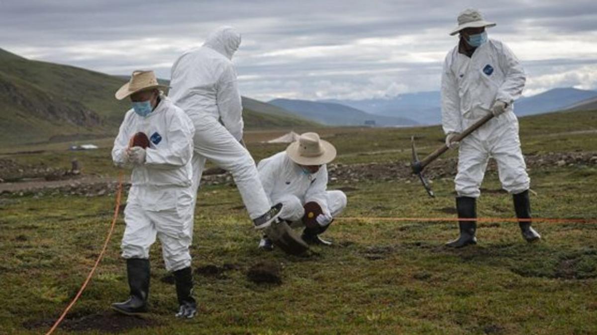Инфекционисты в противочумных костюмах дезинфицируют территорию