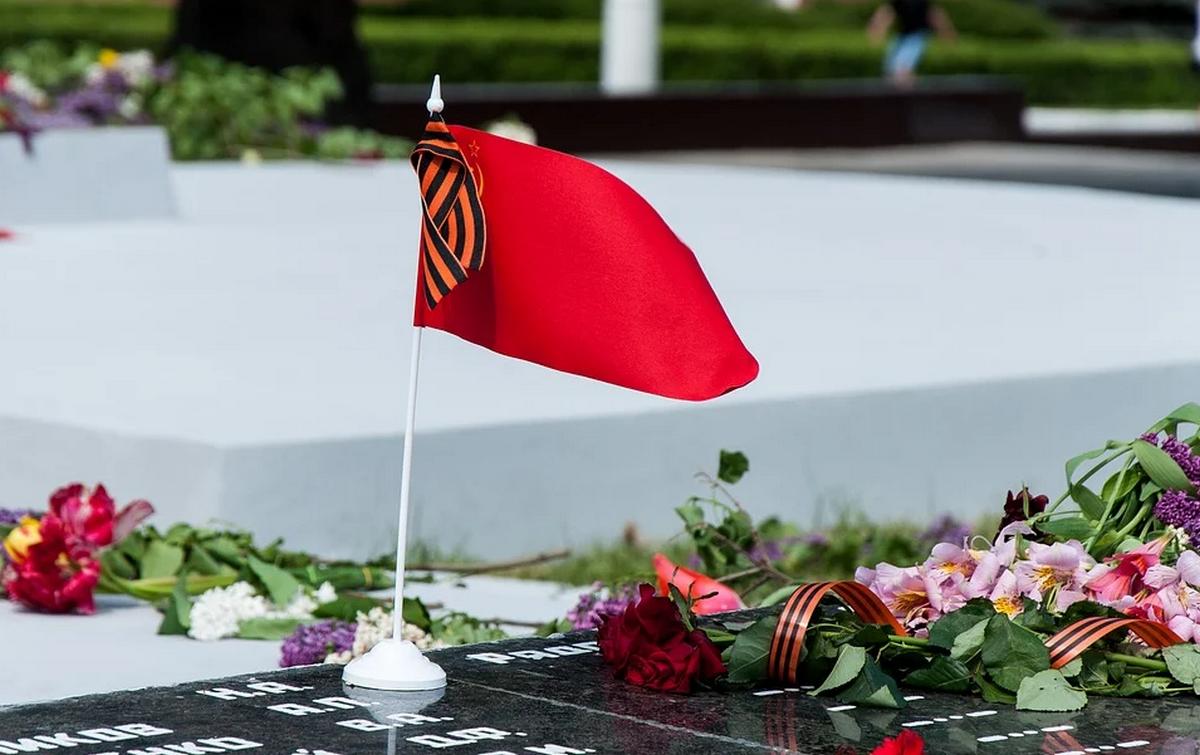 Цветы, красный флажок и георгиевская лента у памятника солдатам Великой Отечественной войны