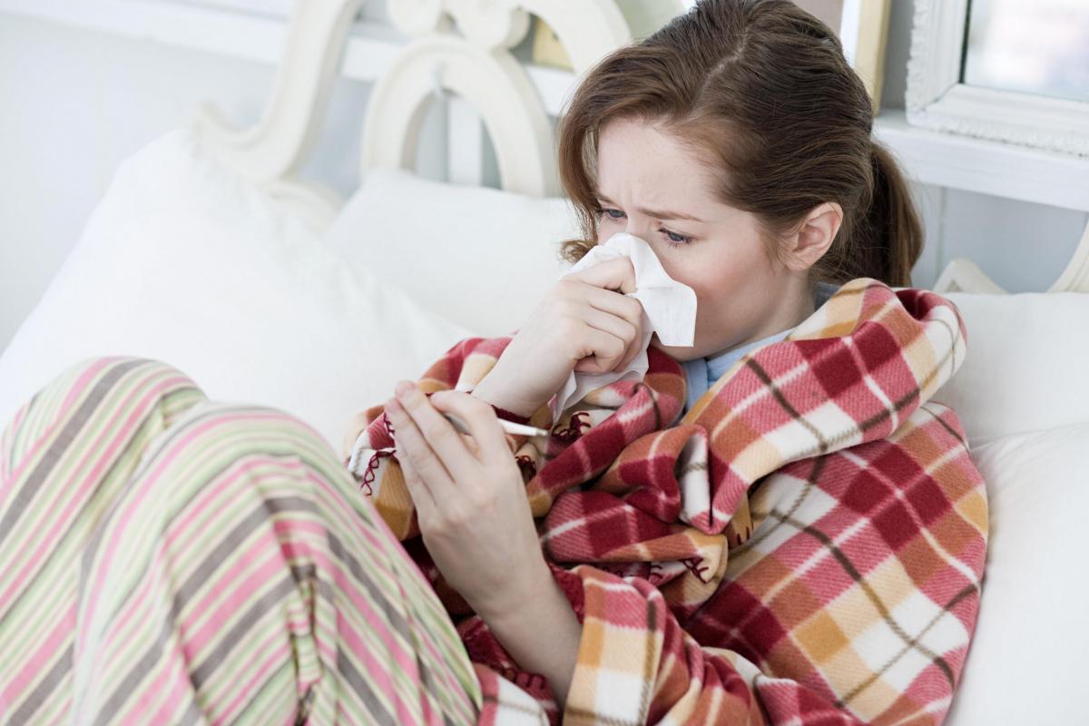 Девушка в постели с термометром