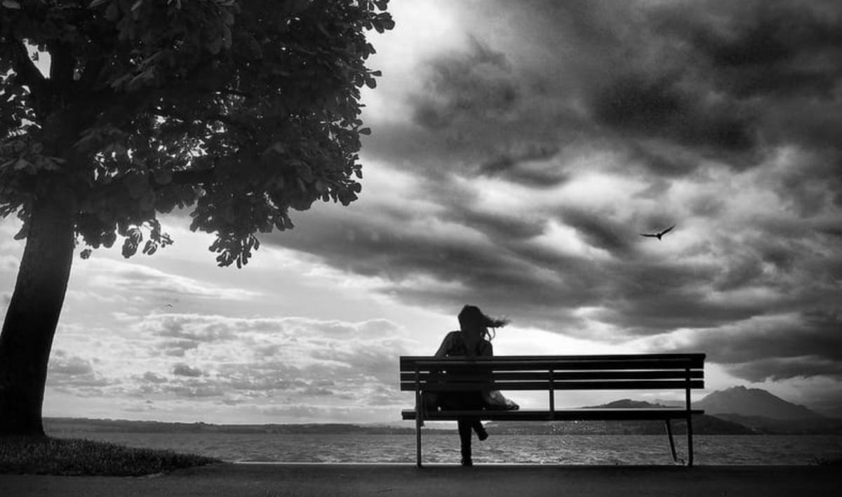 Одинокая девушка на скамейке