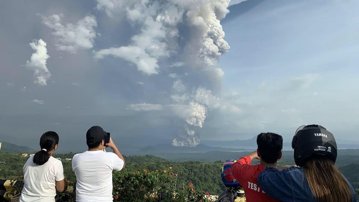 туристы наблюдают за извержением вулкана Тааль